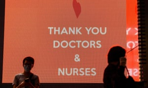 Pedestrians pass an electronic sign with a message of thanks to doctors and nurses in Hong Kong on May 13, 2020.