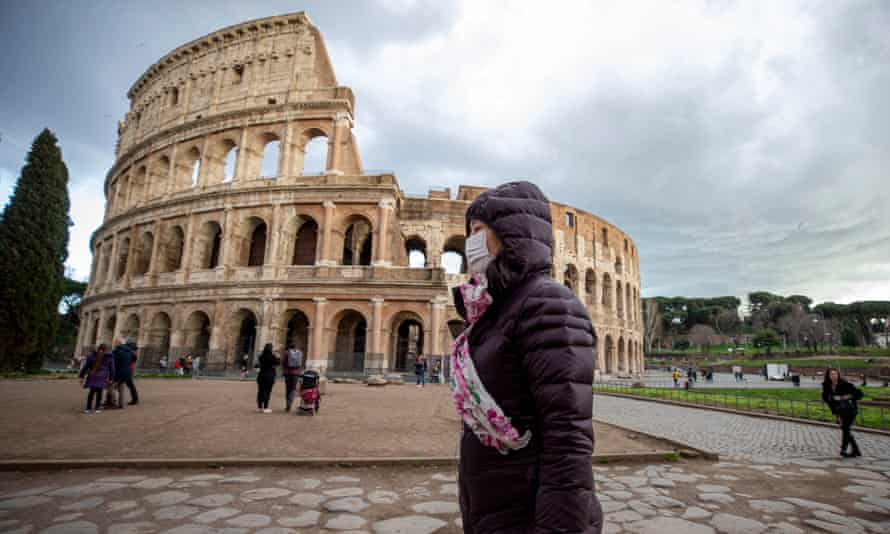 A woman wears a face mask as she walks past the Colosseum in Rome.