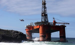 A coastguard helicopter winches a salvage expert onboard the Transocean Winner drilling rig