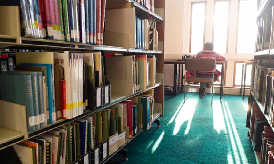 Rear view of a student sitting at a desk studying in the library