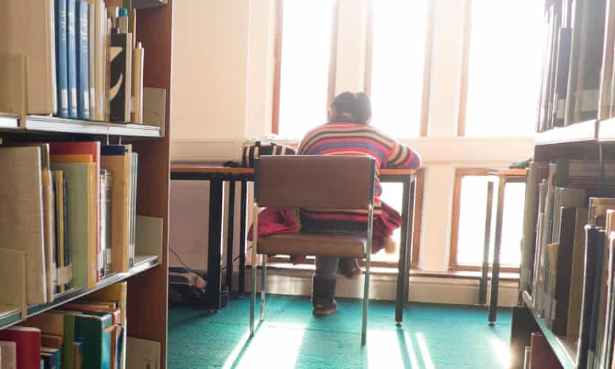 Rear view of a student sitting at a desk studying in the library, Llanbadarn campus, Aberystwyth University.