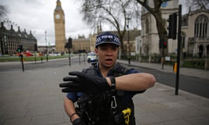 An armed police officer gestures as he stands guard in Parliament Square