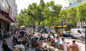 People sit outside a restaurant near the popular shopping street Kurfürstendamm in Berlin.