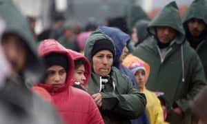 Refugees and migrants wait to cross the Greek-Macedonian border