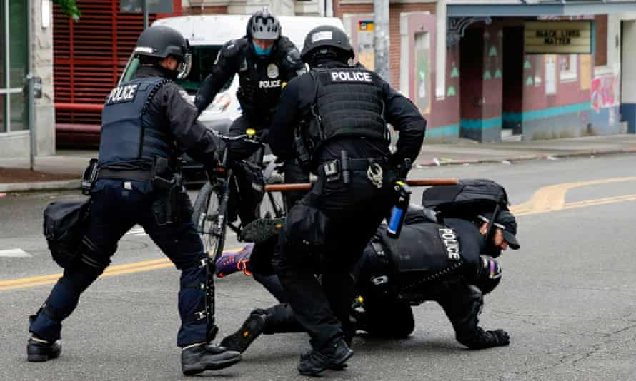 Seattle Police tackle a demonstrator who was blocking the intersection of East Pine Street and 11th Avenue on 1 July.