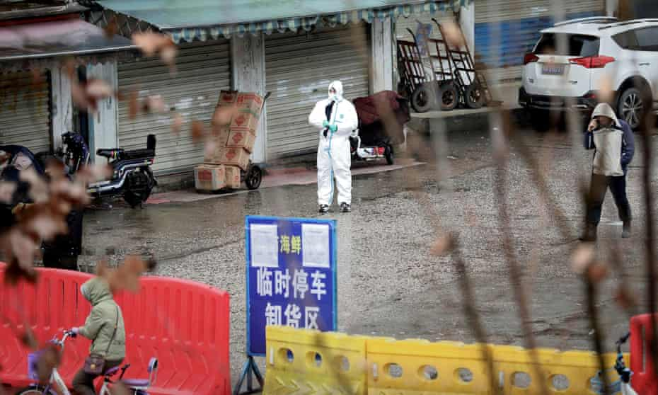 A worker in a protective suit at the closed seafood market in Wuhan on 10 January 2020