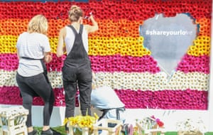 People create a rainbow flag from flowers