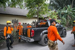 Members of a rescue team search for residents around a hazardous area near the erupting volcano