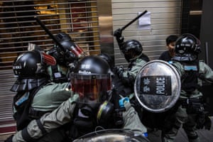 Riot police detain two men in the central district of Hong Kong.