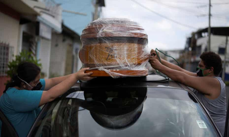 A couple tie an empty coffin to their car to collect the body of a relative in Guayaquil