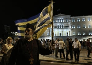 A Greek orthodox priest holds a Greek flag as he takes part in a rally against austerity, supporting the government on the negotiations with its international creditors, in Athens, Greece, 17 June 2015.