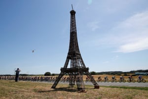 The pack of riders cycles past a replica of the Eiffel Tower.