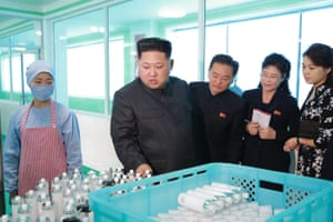 Kim inspecting the Pyongyang Cosmetics Factory, as his wife Ri Sol-Ju looks on.