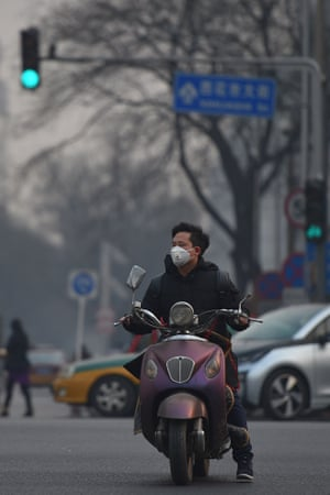 A moped rider cyclist wearing a face mask
