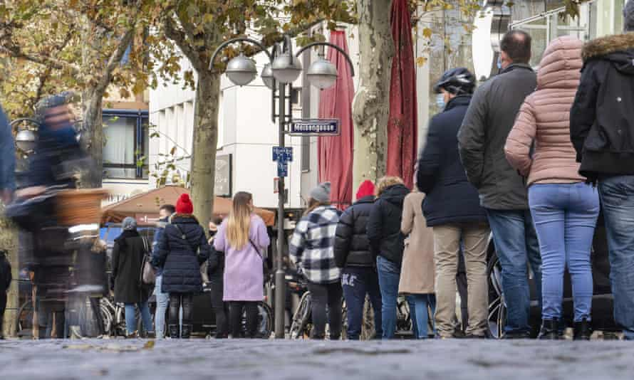 People queue in front of a shop in Frankfurt