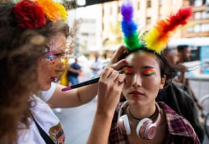 A woman has her makeup done before the parade