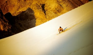 A young man surfs along the sand on the slope.