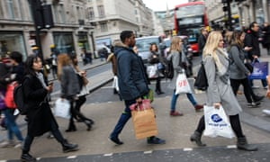Shoppers carry bags as they cross the road along Oxford Street