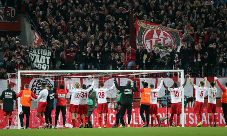 The FC Cologne players celebrate with their fans after beating Bayer Leverkusen 2-0 in December 2019.