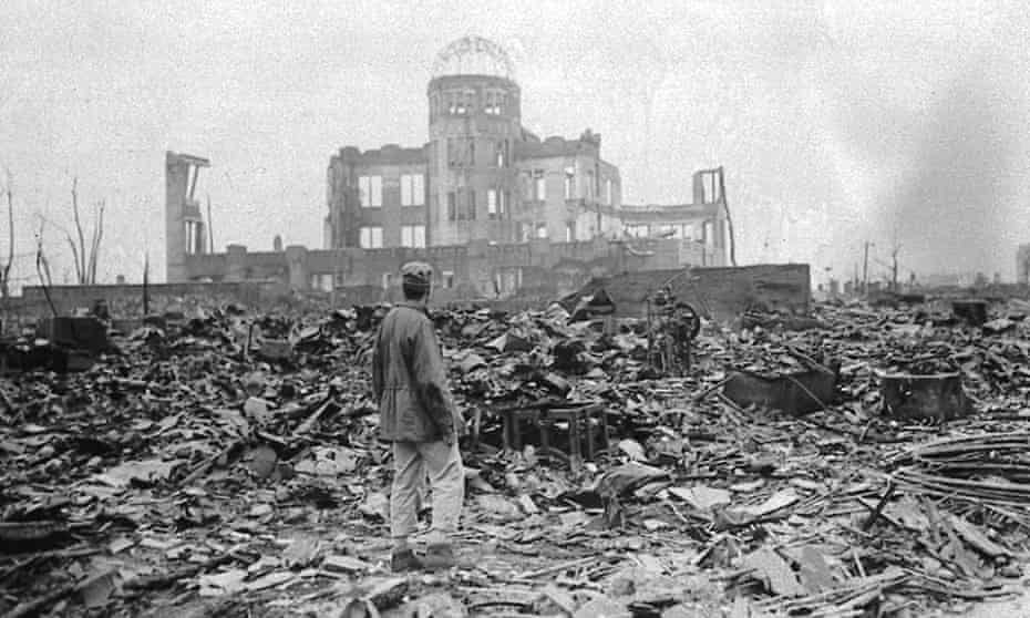 An allied correspondent stands in a sea of rubble before the shell of a building in Hiroshima on 8 September 1945