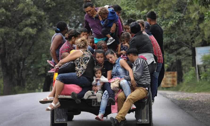 Migrant caravan participants travel north, near Quezaltepeque, Guatemala, on 16 October.