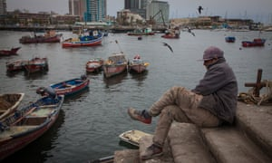 A dock worker waits for fishermen to return to Antofagasta harbour.