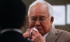 Former Malaysian Prime Minister Najib Razak reacts before leaving Kuala Lumpur High Court after being found guilty on seven charges linked to the 1MDB fraud case.