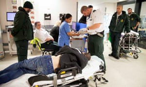 Paramedic Tracy Proud (2nd left, purple hair) along with paramedic colleagues care for an unconscious man who is admitted to A&E