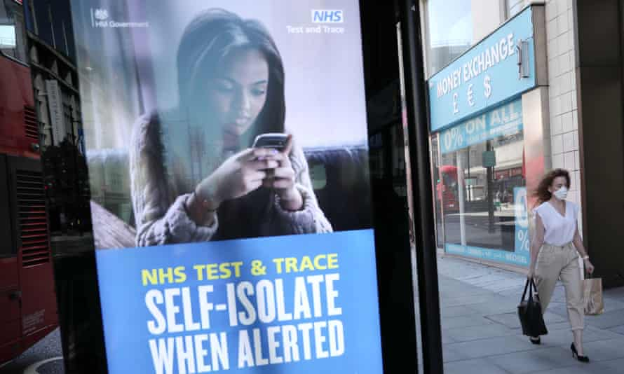 A woman walks past an advert for the test-and-trace system in London