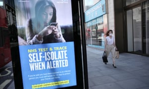 A woman walks past an NHS Test and Trace advertisement on Oxford Street