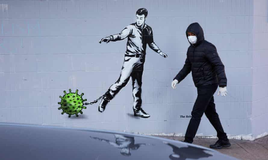 A man walks by a coronavirus mural