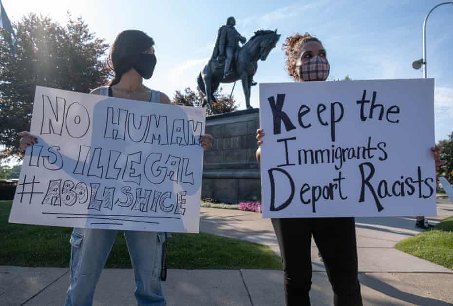 Ruchita Coomar and Katybeth Davis protest I.C.E. in front of the Custer statue in Monroe.