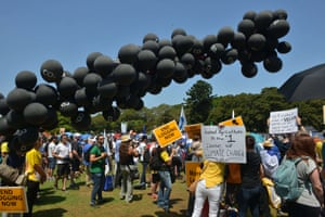 Black balloons float in the air during a rally in Sydney, Australia