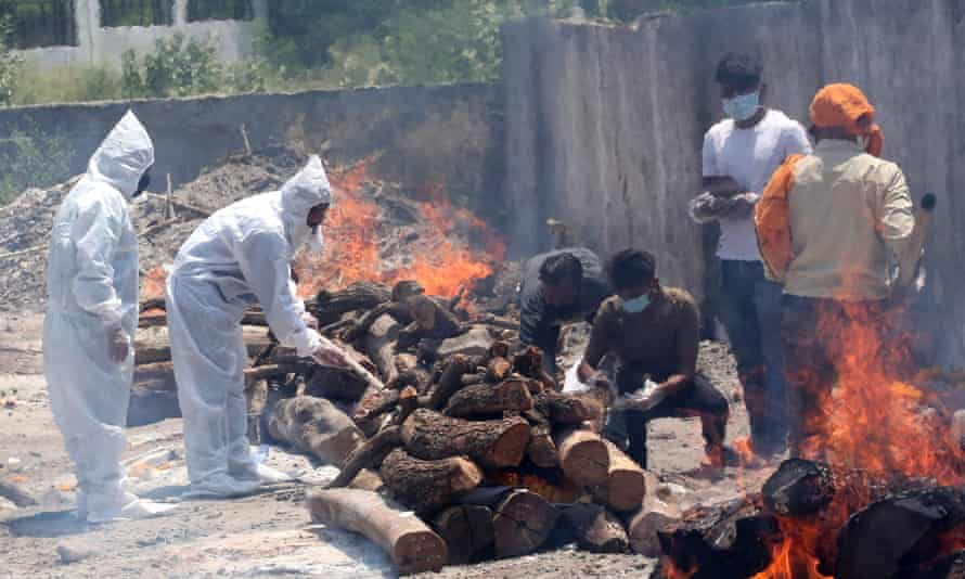 Relatives walk amid burning funeral pyres as they perform last rites for Covid-19 victims in Bhopal.