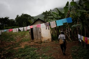 A man walks next to laundry hanging to dry in Boucan Ferdinand