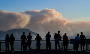 People on a viewing platform watch smoke rise from bushfires in the Blue Mountains near Katoomba, New South Wales, last month.