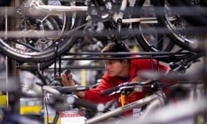 A customer inspects bicycles as they hang on display at a Halfords store