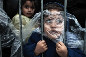 People, first prize, singles - Matic Zorman - A child is covered with a raincoat while she waits in line to register at a refugee camp in Preševo, Serbia