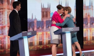 Ed Miiband looks on as Plaid Cymru Party leader Leanne Wood and Scottish National Party leader Nicola Sturgeon embrace after the BBC Challengers' Election Debate 2015 at Central Hall Westminster, London.
