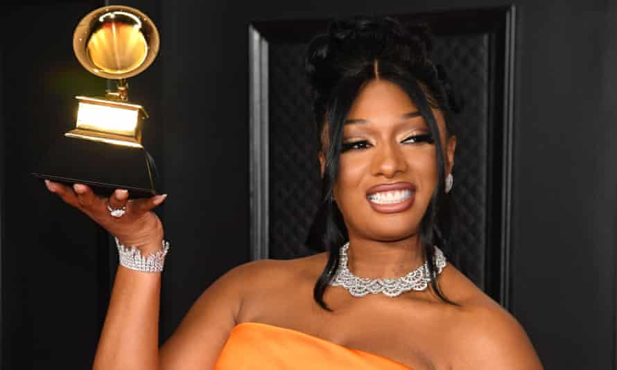 Megan Thee Stallion posing with one of her three new Grammy awards.
