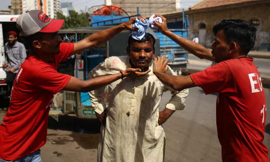 A man attempts to cool off using wet towels at a roadside camp in Karachi