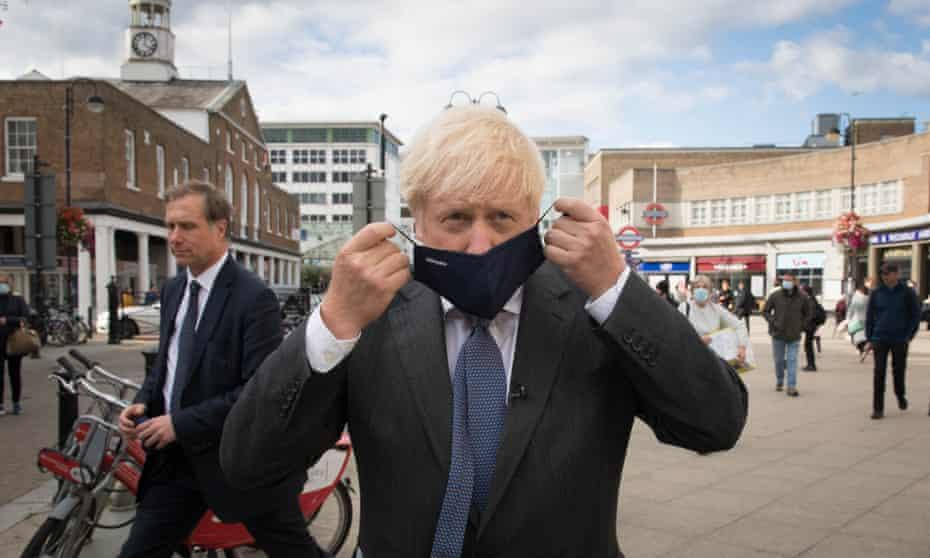 Boris Johnson, close to the camera, put on a face mask as passersby cross behind him in. apublic square