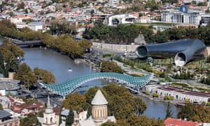 The Bridge of Peace, which some say looks like a discarded sanitary towel; to its right the conjoined concert hall and exhibition centre, and the presidential palace with its glass egg.
