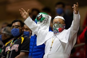 Mazatlán, Mexico: Fans dressed as the pope and a wrestler cheer during a baseball game between Mexico and Panama