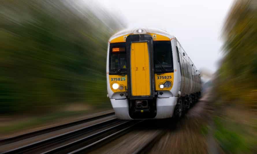 A modern train speeds down a track