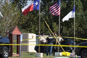 Law enforcement officials stand next to a covered body at the scene of a fatal shooting at the First Baptist church in Sutherland Springs, Texas.