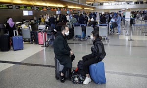 Masked passengers wait to check in at the Los Angeles international airport
