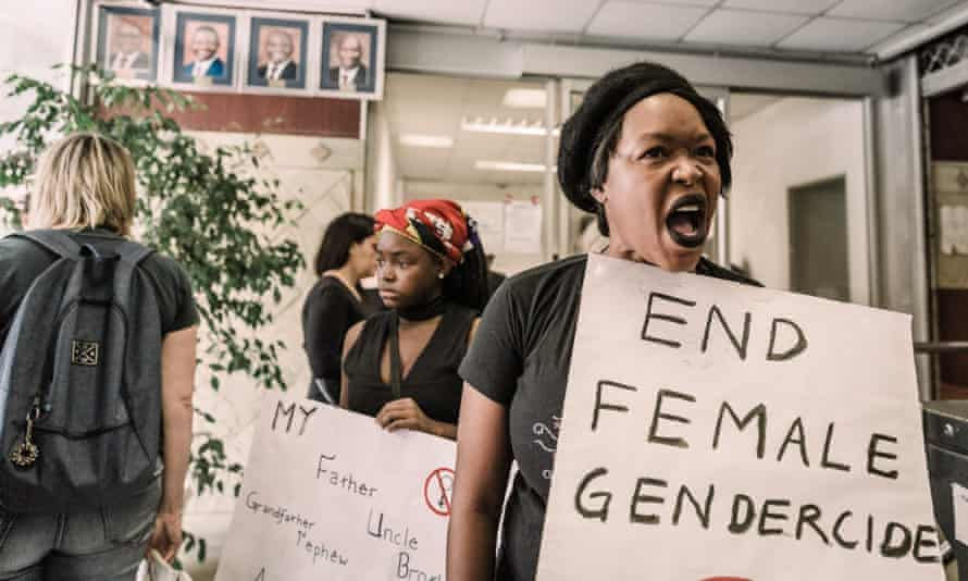 Women hold signs saying 'end female gendercide'.