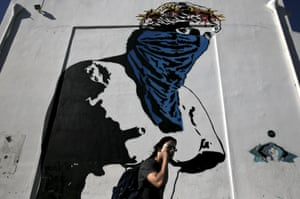 """A man makes his way past graffiti """"Athena vs Europa, Resist vs Submit"""", which depicts the ancient statue of Goddess Aphrodite of Milo wearing a scarf and a wreath consisting of the stars of the European Union flag, made by French street artist Goin in Athens May 25, 2015. Greece intends to make good on its debt obligations but needs aid urgently to be able to do so, the government said on Monday, after several senior officials insisted Athens had no money to pay a loan instalment falling due next week. REUTERS/Alkis Konstantinidis"""