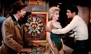 Two men and a woman around a pinball machine